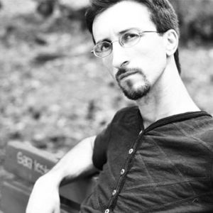 Lo scrittore Emiliano Grisostolo seduto su una panchina a Maniago